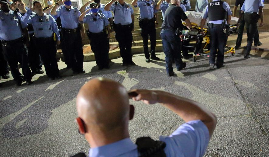 St. Louis police officers line up and salute as the body of fallen Officer Tamarris L. Bohannon is brought to the morgue in St. Louis, Sunday, Aug. 30, 2020. Bohannon died Sunday after being shot in the head by a barricaded gunman on the city's south side, authorities said. (David Carson/St. Louis Post-Dispatch via AP)