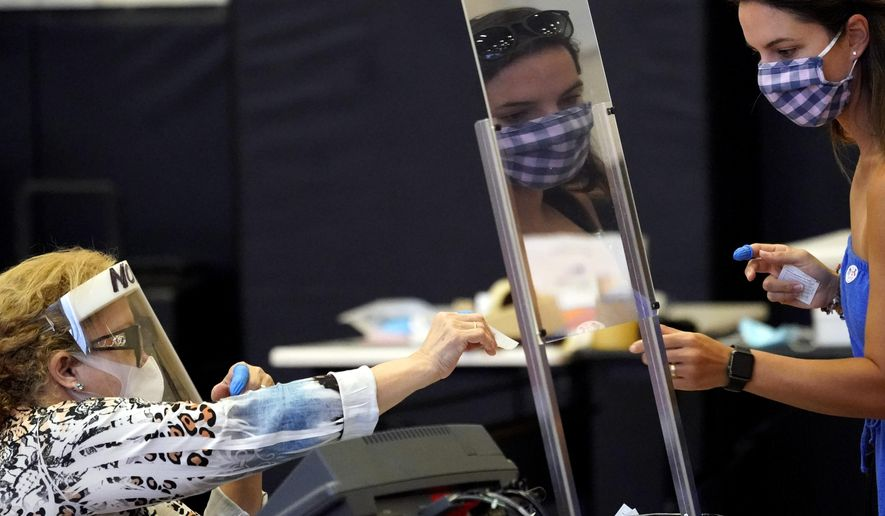 In this June 29, 2020, photo, Harris County election clerk Nora Martinez (left) helps a voter in Houston. Texas is one of only a few states that has not moved to expand mail-in voting in November over pandemic fears. (AP Photo/David J. Phillip) **FILE**
