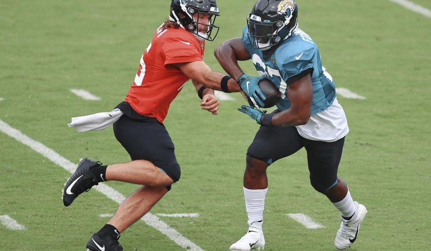 Jacksonville Jaguars starting quarterback Gardner Minshew II, left, hands the ball off to running back Leonard Fournette during NFL football training camp, Saturday, Aug. 29, 2020, in Jacksonville, Fla. (Bob Self/The Florida Times-Union via AP)