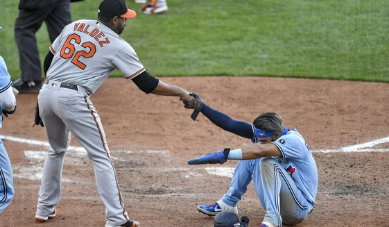 Baltimore Orioles pitcher Cesar Valdez (62) helps Toronto Blue Jays' Lourdes Gurriel Jr. off the ground after he was tagged out at the plate to end a baseball game in the 11th inning in Buffalo, N.Y., Monday, Aug. 31, 2020. Baltimore beat Toronto 4-3. (AP Photo/Adrian Kraus)