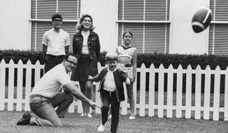 FILE - In this June 1, 1970, file photo, Kansas City Chiefs owner Lamar Hunt watches after holding the ball for his son, Clark, 5, to kick in the family backyard in Dallas. Behind them is Hunt's children by a former marriage, Lamar Jr. 13, left, and Sharon, 12, right. His wife Norma is at center rear. Lamar Hunt was a champion of Black rights during the Civil Rights era of the 1960s. He grew up in conservative circles yet formed his own opinions of right and wrong. And when his football-loving son was born in 1965, those principles that Hunt instilled in his football franchise became instilled in Clark, who years later would take succeed him as chairman of the Chiefs. (AP Photo/File)