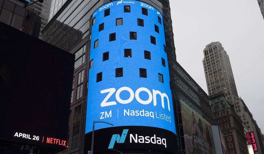 FILE - This April 18, 2019, file photo shows a sign for Zoom Video Communications ahead of the company's Nasdaq IPO in New York. Zoom's videoconferencing service is deepening its integral role in life during the coronavirus pandemic as tens of thousands more businesses and other users pay for subscriptions to get more control over their virtual meetings. The surge in paying customers enabled Zoom to hail another quarter of astounding growth in a report released Monday, Aug. 31, 2020. (AP Photo/Mark Lennihan, File)