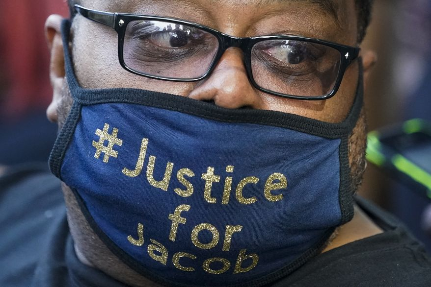 In this Aug. 29, 2020, file photo, Jacob Blake's father, Jacob Blake Sr. wears a justice for Jacob mask at a rally in Kenosha, Wis. Mr. Blake's social-media posts have come under scrutiny for anti-Semitic and anti-Catholic content. (AP Photo/Morry Gash, File)  **FILE**