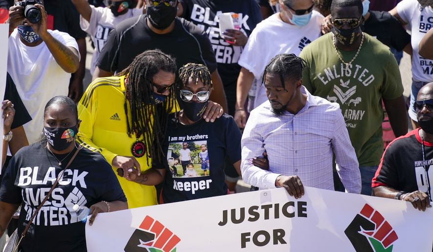In this Aug. 29, 2020, file photo, Jacob Blake's sister Letetra Widman, center, and uncle Justin Blake, left, march at a rally for Jacob Blake Saturday, Aug. 29, 2020, in Kenosha, Wis. Authorities have been reluctant to release even the most basic information about the incident or details about the white officer who shot Blake seven times in the back. (AP Photo/Morry Gash, File)  **FILE**