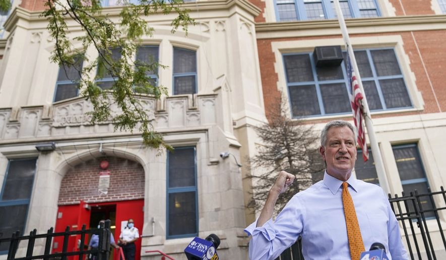 In this Aug. 19, 2020, photo, New York Mayor Bill de Blasio speaks to reporters after visiting New Bridges Elementary School to observe pandemic-related safety procedures, in the Brooklyn borough of New York. (AP Photo/John Minchillo) **FILE**