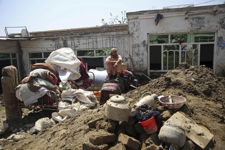 An Afghan man sits amid the belongings from his house that was damaged by a mudslide, in Parwan province, north of Kabul, Afghanistan, Thursday, Aug. 27, 2020. The death toll from heavy flooding in northern and eastern Afghanistan rose to at least 150 on Thursday, with scores more injured as rescue crews searched for survivors beneath the mud and rubble of collapsed houses, officials said. (AP Photo/Rahmat Gul)