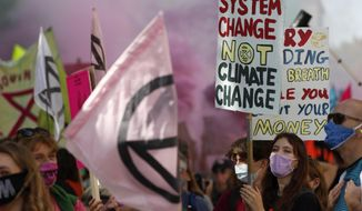 Demonstrators hold posters and flags during an Extinction Rebellion climate change protest in London, Tuesday, Sept 1, 2020. (AP Photo/Alastair Grant)