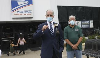 U.S. Sen. Bob Casey, D-Pa., left, and Kevin Gallagher, vice president of the Pennsylvania Postal Workers Union answer questions about operations at a United States Post Office in Scranton, Pa., shortly after a tour on Monday, Aug. 17, 2020. The facility has had two mail sorters removed and a third is being dismantled. (Jake Danna Stevens/The Times-Tribune via AP)