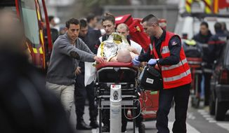 FILE - In this Jan. 7, 2015 file photo, an injured person is transported to an ambulance after a shooting at the French satirical newspaper Charlie Hebdo's office, in Paris. The January 2015 attacks against Charlie Hebdo and, two days later, a kosher supermarket, touched off a wave of killings claimed by the Islamic State group across Europe. Seventeen people died along with the three attackers. Thirteen men and a woman accused of providing the attackers with weapons and logistics go on trial on terrorism charges Wednesday Sept. 2, 2020. (AP Photo/Thibault Camus, File)