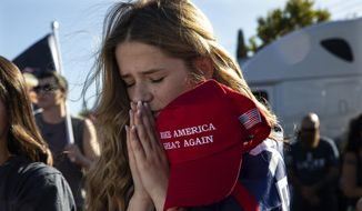 Liza Durasenko, 16, from Oregon City, Ore., prays during a rally in support of President Donald Trump, Aug. 29, 2020, in Clackamas, Ore. (AP Photo/Paula Bronstein) ** FILE **