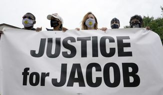 Participants in a community gathering at the site of Jacob Blake's shooting hold a sign in support of justice during speeches Tuesday, Sept. 1, 2020, in Kenosha, Wis. President Donald Trump plans to visit Kenosha later in the day. (AP Photo/Morry Gash)
