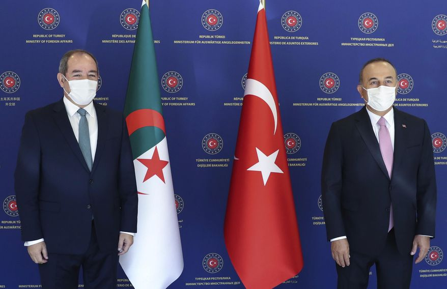 Turkey's Foreign Minister Mevlut Cavusoglu, right, and Algeria's Foreign Minister Sabri Boukadoum pose for photos before their talks, in Ankara, Turkey, Tuesday, Sept. 1, 2020. (Cem Ozdel/Turkish Foreign Ministry via AP, Pool)