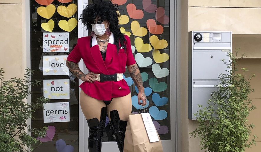 """This Friday, Aug. 28, 2020, photo shows Kochina Rude delivering food for customers in San Francisco. A San Francisco drag show night club has taken the show on the road after having to close its doors due to the coronavirus pandemic. Oasis' """"Meals on Heals"""" is dispatching drag queens to deliver food, custom cocktails and socially-distant lip synch performances. (AP Photo/Haven Daley)"""