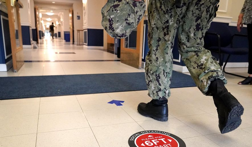 A social distancing sign is seen on the floor as a midshipman walks to class at Luce Hall at the U.S. Naval Academy, Monday, Aug. 24, 2020, in Annapolis, Md. Under the siege of the coronavirus pandemic, classes have begun at the Naval Academy, the Air Force Academy and the U.S. Military Academy at West Point. But unlike at many colleges around the country, most students are on campus and many will attend classes in person. (AP Photo/Julio Cortez)