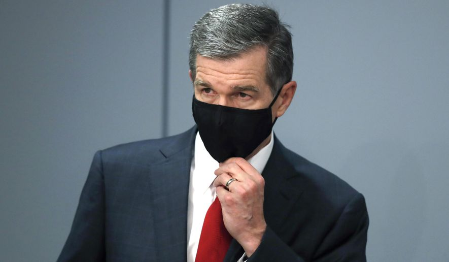 Gov. Roy Cooper adjust his mask as he listens to Dr. Mandy Cohen, secretary of the North Carolina Department of Health and Human Services, speak during a briefing at the Emergency Operations Center in Raleigh, N.C., Tuesday, Sept. 1, 2020. (Ethan Hyman/The News & Observer via AP)