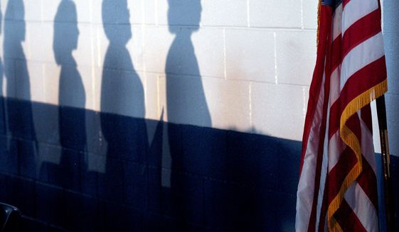 Schoolchildren honor the flag during the playing of the National Anthem in this Sept. 11, 2008, file photo. (Associated Press file photo)  **FILE**