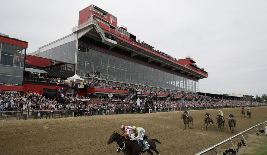 In this May 20, 2017, file photo, Cloud Computing, front left, ridden by Javier Castellano, slows after winning the 142nd Preakness Stakes next to Classic Empire (5), with Julien Leparoux, at Pimlico in Baltimore. The Preakness will be run at Pimlico on Oct. 3 without fans. The decision not to allow fans means it will be a spectator-free sweep of the three Triple Crown races this year because of the global pandemic. (AP Photo/Matt Slocum, File)  **FILE**
