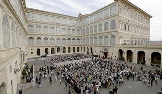 Faithful listen to Pope Francis, white figure sitting at center right, during his general audience, the first with faithful since February when the coronavirus outbreak broke out, at the San Damaso courtyard, at the Vatican, Wednesday, Sept. 2, 2020. (AP Photo/Andrew Medichini)