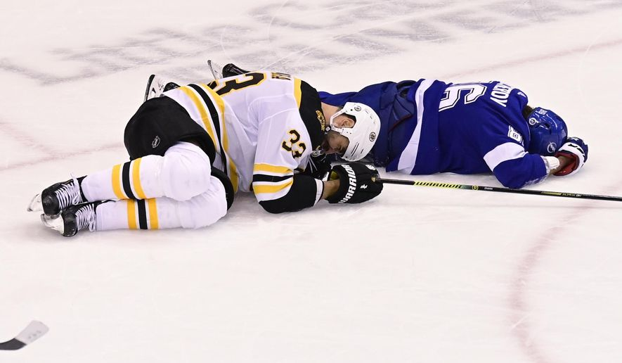 Boston Bruins defenseman Zdeno Chara (33) and Tampa Bay Lightning right wing Nikita Kucherov (86) lie on the ice after Chara blocked a shot and Kucherov caught a high stick during first-period NHL Stanley Cup Eastern Conference playoff hockey game action in Toronto, Monday, Aug. 31, 2020. (Frank Gunn/The Canadian Press via AP)