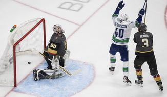 Vancouver Canucks' Elias Pettersson (40) celebrates a goal on Vegas Golden Knights goalie Robin Lehner (90), next to Brayden McNabb (3) during the third period of Game 5 of an NHL hockey second-round playoff series, Tuesday, Sept. 1, 2020, in Edmonton, Ontario. (Jason Franson/The Canadian Press via AP)