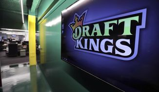 In this May 2, 2019, file photo, the DraftKings logo is displayed at the sports betting company headquarters in Boston.  DraftKings shares jumped 4% in morning trading, Wednesday, Sept. 2, 2020 after announcing that basketball legend Michael Jordan would take an ownership stake in the company in exchange for becoming a special adviser to the sports betting site.  (AP Photo/Charles Krupa, File)  **FILE**