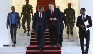 """FILE - In this Tuesday, Feb. 18, 2020 file photo, U.S. Secretary of State Mike Pompeo, center right, walks with Ethiopia's Prime Minister Abiy Ahmed, center-left, after meeting at the Prime Minister's office in Addis Ababa. The State Department said Wednesday, Sept. 2, 2020 that on the guidance of President Donald Trump the U.S. is suspending some aid to Ethiopia over the """"lack of progress"""" in talks with Egypt and Sudan over a massive, disputed dam project which Egypt has called an existential threat and worries will reduce the country's share of Nile waters. (Andrew Caballero-Reynolds/Pool via AP, File)"""