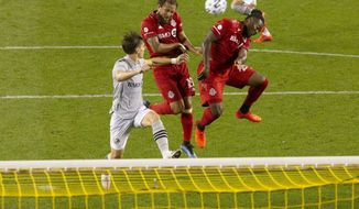Toronto FC midfielder Nick DeLeon, center, gets between Montreal Impact's Jukka Raitala, left, and TFC's Ayo Akinola only to send his header wide during the second half of an  MLS soccer match in Toronto, Ontario, Tuesday, Sept. 1, 2020. (Chris Young/The Canadian Press via AP)