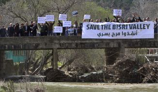 """Lebanese protesters hold placards during a protest against the Bisri dam project, in the Bisri Valley, 58 kilometers (36 miles) southeast of Beirut, Lebanon, Sunday, March. 10, 2019. The valley of Bisri in Lebanon lies on a green fertile bed, a spot that has cradled civilizations dating as far back as the Bronze Age. Its expansive lands of pine, citrus trees and ancient ruins are about to turn into a controversial mega dam funded by the World Bank. For years now, activists and locals have voiced their opposition to what they describe as not only """"an environmental crime,"""" but also a project that mirrors Lebanon's governance crisis. (AP Photo/Mohammed Zaatari)"""