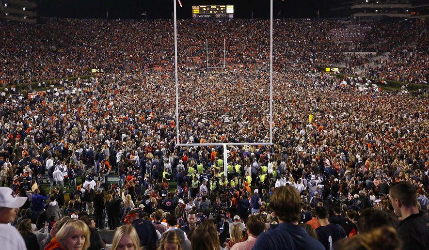 Fans rush the field after Auburn defeated Alabama in the Iron Bowl NCAA college football game, Saturday, Nov. 25, 2017, in Auburn, Ala. What is most commonly referred to as major college football (aka NCAA Division I Bowl Subdivision or FBS) is compromised of 130 teams and 10 conferences. Seventy-seven of those teams are scheduled to play throughout the fall, starting at various times in September. The other 53, including the entire Big Ten and Pac-12, have postponed their seasons and are hoping to make them up later. That means no No. 2 Ohio State, No. 7 Penn State, No. 9 Oregon and six other teams that were ranked in the preseason AP Top 25. (AP Photo/Brynn Anderson, File)  **FILE**
