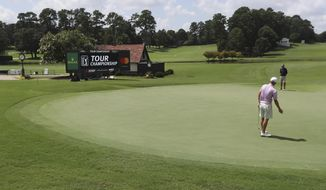 Justin Thomas and his instructor are the only ones around to react to his putt on the 18th green during his practice round for the season-ending Tour Championship at East Lake Golf Club on Wednesday, Sept. 2, 2020, in Atlanta. (Curtis Compton/Atlanta Journal-Constitution via AP) **FILE**