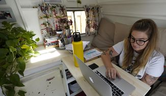 Kelly Mack works on her laptop to teach remotely from her early 1940s vintage camper/trailer in her backyard at home in Evanston, Ill., Wednesday, Sept. 2, 2020. Most students in Illinois have been starting remote learning this fall, according to results from an Illinois State Board of Education survey. Mack teaches math at Nichols Middle School in Evanston. (AP Photo/Nam Y. Huh)