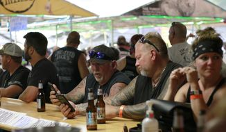 FILE - In this Aug. 7, 2020 file photo, people congregate at One-Eyed Jack's Saloon during the 80th annual Sturgis Motorcycle Rally in Sturgis, S.D.. Hundreds of thousands of people attended the Sturgis Motorcycle Rally in South Dakota from Aug. 7 to 16. Minnesota health officials reported Wednesday, Sept. 2, 2020, that a man in his 60s who attended the rally died from COVID-19. (AP Photo/Stephen Groves File)