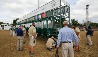 Crews ready a new starting gate at Churchill Downs on Tuesday, Sept. 1, 2020, in Louisville, Ky. The starter and assistant starters were giving the new gate a test run for the mile-and-a-quarter race. The new starting gate will allow 20 horses to be loaded for the Kentucky Derby. The track has previously used two gates to accommodate the large field for the event. The gate will be used only for the Kentucky Derby. (Michael Clevenger/Courier Journal via AP)  **FILE**
