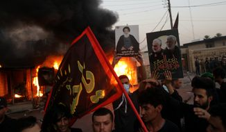 Supporters of an Iran-backed militia hold posters of Iranian General Qassem Soleimani, deputy commander Abu Mahdi al-Muhandis and Grand Ayatollah Ali al-Sistani, center, while burning the building of Dijala local TV channel accusing it of broadcasting songs and dance on the holy Shiite day of Ashoura in Baghdad, Iraq, Monday, Aug. 31, 2020. (AP Photo/Khalid Mohammed)