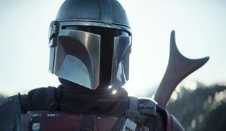 """This image released by Disney Plus shows Pedro Pascal in a scene from """"The Mandalorian."""" An announcement on the Star Wars Twitter account Wednesday said new episodes would be available on Disney+ starting on Oct. 30. (Disney Plus via AP)"""