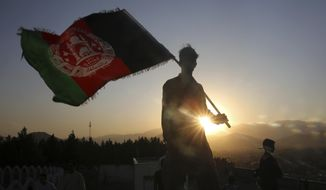 In this Aug. 19, 2019, file photo, a man waves an Afghan flag during Independence Day celebrations in Kabul, Afghanistan. Officials on both sides of Afghanistan's protracted conflict say efforts are ramping up for the start of intra-Afghan negotiations, a critical next step to a U.S. negotiated peace deal with the Taliban. (AP Photo/Rafiq Maqbool, File)