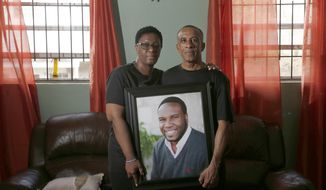 FILE - In this Sept. 25, 2018 file photo, Allison and Bertrum Jean pose as they hold a portrait of their late son Botham Shem Jean at their home in Castries, St. Lucia. The family of Botham Jean, who was fatally shot by an off-duty Dallas police officer who said she mistook his apartment for hers is suing the complex where he was killed, saying his door lock didn't work properly. The parents and sister of Botham Jean filed the lawsuit Tuesday, Sept. 1, 2020, in Dallas County district court. (Vernon Bryant/The Dallas Morning News via AP, File)