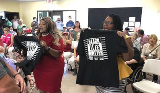 Triana Arnold Gaines, left, and Nselaa Ward hold up Black Lives Matter T-shirts as they protest a speech by U.S. Sen. Kelly Loeffler, Thursday, Sept 3, 2020, in Cumming, Ga. Gaines and Ward kept Loeffler from finishing a campaign speech. (AP Photo/Jeff Amy)