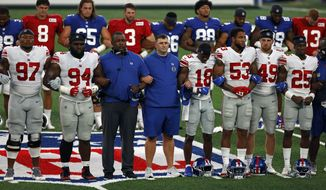 FILE - New York Giants head coach Joe Judge, center, stands with arms linked with his players to make a social injustice statement prior to their scrimmage at the NFL football team's training camp in East Rutherford, N.J., Friday, Aug. 28, 2020. A long-time advocate of the right to protest for social change and equality, New York Giants co-owner John Mara admits he was stunned listening to his players talk about their experiences with police and authorities in the wake of the death George Floyd in June. (AP Photo/Adam Hunger, File)