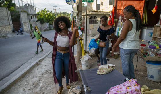 Transgender Semi Kaefra Alisha Fermond smiles after receiving a lollipop from neighborhood street vendors as she makes her way to the Kay Trans Haiti center to celebrate her 24th birthday, in Port-au-Prince, Haiti, Friday, Aug. 7, 2020. Prejudice and discrimination against transgender people is common in Haiti, but the Kay Trans Haiti center is providing a haven where transgender people can feel welcome and accepted. (AP Photo/Dieu Nalio Chery)