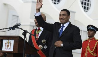 FILE - In this March 3, 2016 file photo, Jamaican Prime Minister Andrew Holness waves to the crowd after being sworn into office, in Kingston, Jamaica.   Polls show Holness'  Jamaica Labour Party, JLP, with double-digit leads over the center-left opposition, more than enough to maintain the JLP's parliamentary majority in  the Thursday, Aug. 3, 2020 election. (AP Photo/Collin Reid, File)