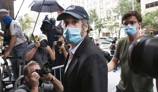 "FILE - This July 24, 2020, file photo shows Michael Cohen, center, President Donald Trump's former personal attorney, returning to his apartment, in New York, after being released from prison. So-called Son of Sam laws won't keep Cohen from profiting from any part of his book, ""Disloyal: The True Story of the Former Personal Attorney to President Donald J. Trump,"" legal experts told The Associated Press, even if his memoir amounted to a how-to manual for tax evasion and campaign finance violations. (AP Photo/Mark Lennihan, File)"