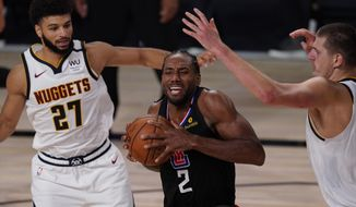 Los Angeles Clippers' Kawhi Leonard (2) moves between Denver Nuggets' Jamal Murray (27) and Nikola Jokic, right, in the second half of an NBA conference semifinal playoff basketball game Thursday, Sept 3, 2020, in Lake Buena Vista Fla. (AP Photo/Mark J. Terrill)