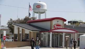 In this May 7, 2020, file photo, workers enter and leave the Tyson Foods pork processing plant in Logansport, Ind. Tyson Foods is planning to open medical clinics at several of its U.S. plants to improve the health of workers at the same time it is under pressure to better protect them from the coronavirus. (AP Photo/Michael Conroy, File) **FILE**