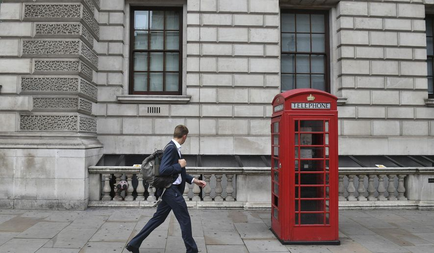 """A man walks past the Department for Digital, Culture, Media and Sport in London's Whitehall, around the old normal morning time 'rush hour', in central London, Thursday Sept. 3, 2020.  Workers are being encouraged to return to their offices, with a Government information campaign reminding people about the efforts taken to make workplaces safe and """"Covid-secure"""".  (Victoria Jones/PA via AP)"""
