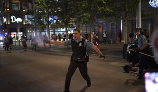 "In this Aug. 26, 2020, file photo, police spray a substance to clear the area where a colleague was down on the Nicollet Mall in Minneapolis. Two men from Minnesota and North Carolina who prosecutors say are members of an anti-government extremist group have been charged with terrorism counts for allegedly building weapons they believed were going to Hamas. They are allegedly members of the ""Boogaloo Bois."" The investigation into the men began after they posted messages on social media about inciting violence after the May 25 death of George Floyd. (Jeff Wheeler/Star Tribune via AP, File)"