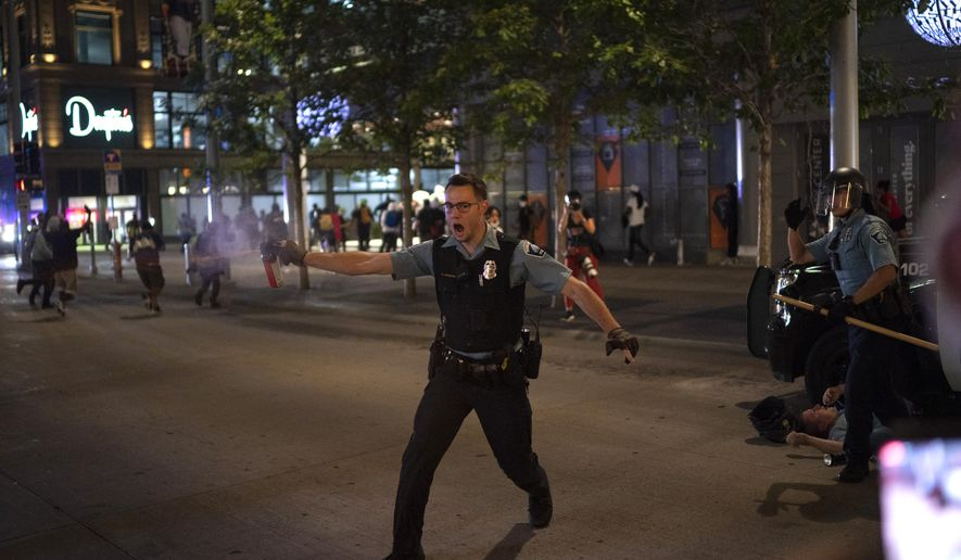 """In this Aug. 26, 2020, file photo, police spray a substance to clear the area where a colleague was down on the Nicollet Mall in Minneapolis. Two men from Minnesota and North Carolina who prosecutors say are members of an anti-government extremist group have been charged with terrorism counts for allegedly building weapons they believed were going to Hamas. They are allegedly members of the """"Boogaloo Bois."""" The investigation into the men began after they posted messages on social media about inciting violence after the May 25 death of George Floyd. (Jeff Wheeler/Star Tribune via AP, File)"""