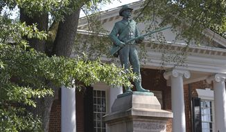 """A bronze statue of an unnamed Confederate soldier, titled """"At Ready,"""" stands outside of the Albemarle County Courthouse on Thursday, Sept. 3, 2020, in Charlottesville, Va. The 1909 statue, two cannons and several cannonballs will be removed Sept. 12. (Erin Edgerton/The Daily Progress via AP)"""