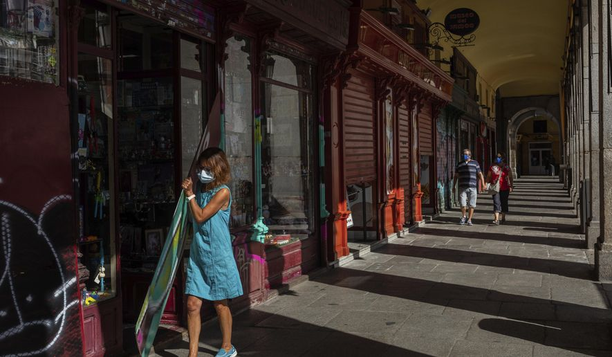 A woman, wearing protective masks to prevent the spread of the coronavirus, opens a commercial store in the Plaza Mayor, in the center of Madrid, Spain, Thursday, Sept. 3, 2020. The Madrid region is a coronavirus hot spot, with almost 32,000 new cases officially recorded over the past two weeks. (AP Photo/Bernat Armangue)