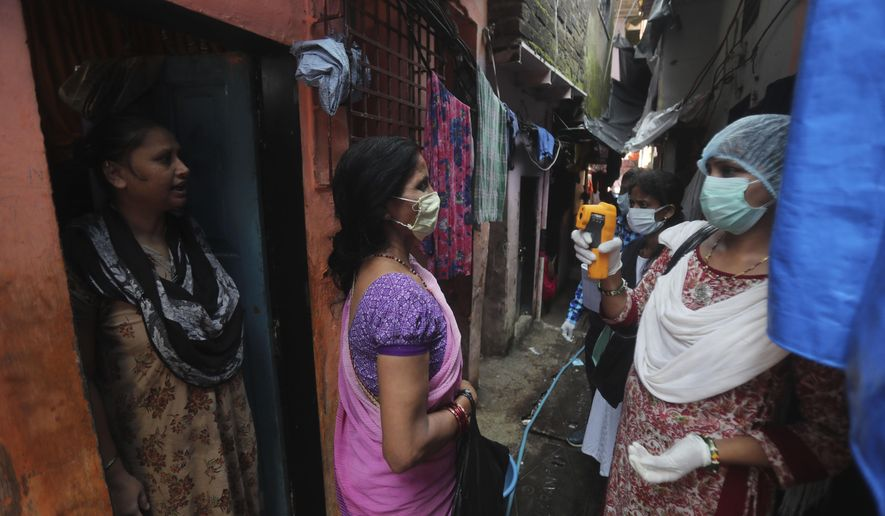 A health worker screens people for symptoms of COVID-19 in Dharavi, one of Asia's biggest slums, in Mumbai, India, Friday, Sept. 4, 2020. The number of people infected with the coronavirus in India rose by another 80,000 and is near Brazil's total, the second-highest in the world. (AP Photo/Rafiq Maqbool)